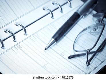 binder, pen and glasses. blue toning