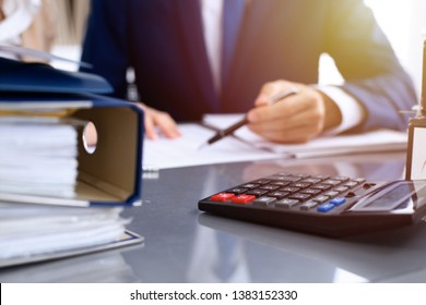 Binders with papers waiting to be processed with businessman or bookkeeper back in blur. Accounting planning budget. Audit, insurance  and business concept