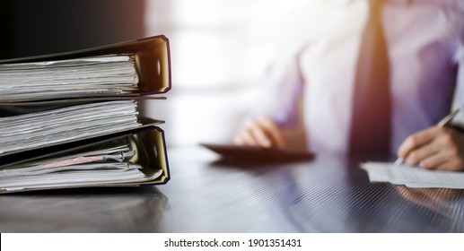 Binders with papers are waiting to be processed by unknown man accountant in blue shirt staying at home during covid pandemic