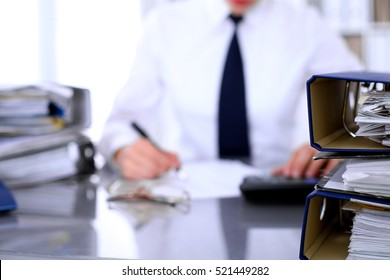Binders with papers are waiting to be processed with business woman back in blur. Accounting planning budget, audit and  insurance concept