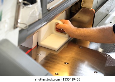 Bindery. Paper trimming on a guillotine.