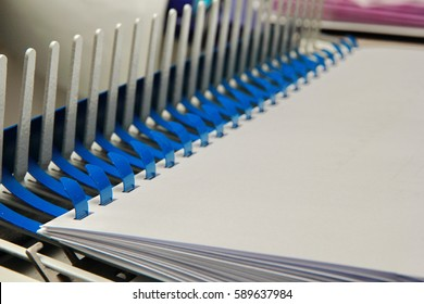Binding documents with plastic ring binder by using ring binding machine for report preparation.