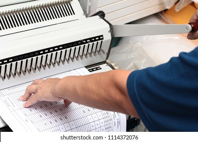 Binding documents ,Use your left hand to push the paper into the drill and used his right hand to press the gear lever punched paper.