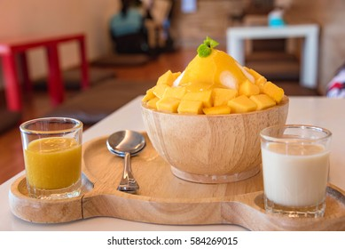 """Bing su"" Korean style fresh mango shaved ice on wood table"