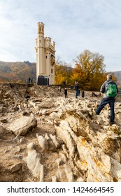 Bingen, Germany - 06.11.2019: Binger Mäuseturm during low water of the Rhine. The rocks in the front are normally under water. The Mäuseturm is build on a small isle in Rhine Gorge.