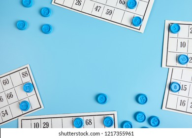 Bingo balls and cards on blue background with copy space.