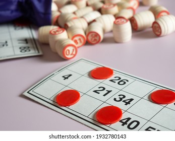 A Bingo board game. Wooden kegs of lotto, playing cards for playing lotto with a bag on a pale lilac background