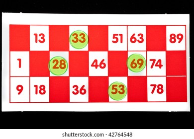 Bingo card with four numbers covered up by green counters