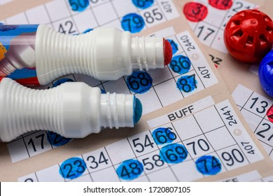 Bingo cards with red and blue markers close up