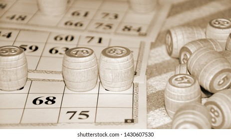 Bingo or lotto game. Wooden kegs of lotto on cards. Cards and chips for playing bingo on a white table.