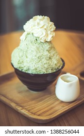 Bingsoo traditional ingredients are, shaved ice, ice cream, in this black cup are green tea bingsoo with whipped cream on top and have condensed milk in a cup ceramic all placed on a wooden tray.