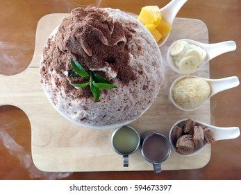 Bingsu dessert (Korea finely ground milky ice) flavored with chocolate powder and fruit topping which includes mango, banana and cookies filled with dry iced at the bottom