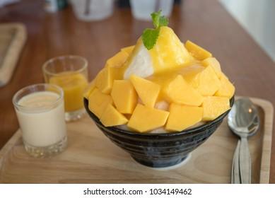 Bingsu ( Korea food) mango served with sweetened condensed milk on table, Mango Bingsu Korea dessert poured mango sauce.