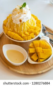 Bingsu ( Korea food) mango served with sweetened condensed milk on table, Mango Bingsu Korea dessert poured mango sauce.