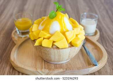 Bingsu ( Korea food) mango served with sweetened condensed milk on table