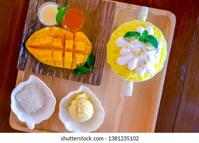 Bingsu (Korean dessert style) refreshing dessert served with mango fruit sticky rice, ice cream and sweetened condensed milk on the wooden plate.