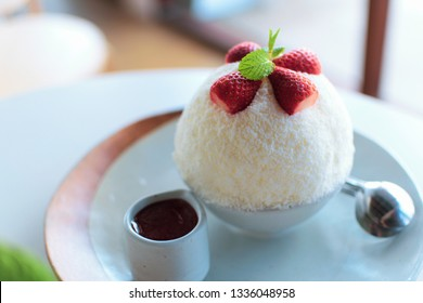 Bingsu decorated with sliced fresh strawberries and mint leaves.