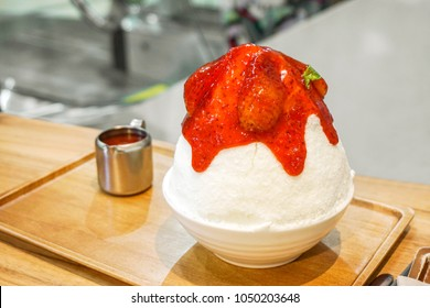 Bingsu strawberry (Frozen cow's milk make spinning to snow flake and topped with strawberry syrup.)(Sweet of Korea.) in white ceramic bowl on wooden tray and table with cup stainless in cafe.
