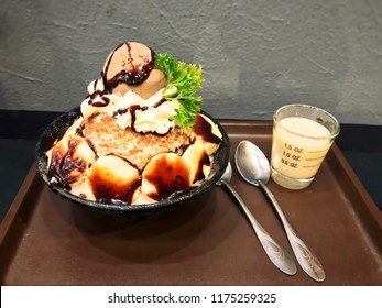 Bingsu with topping such as Chocolate icecream,  banana, wipping cream, vegetable on cup with Condensed milk and spoon put on tray. Patbingsu, Korean shaved ice dessert, Kakigori. Frozen Dessert.
