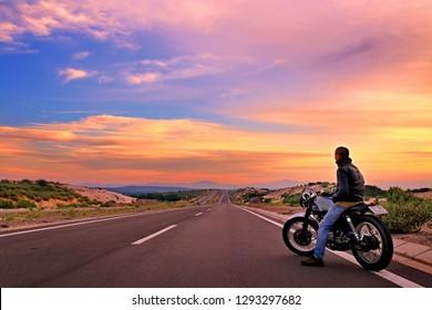 Binh Thuan province, Vietnam - September 02, 2016: Man riding motobike on asphal way in brilliant sunset