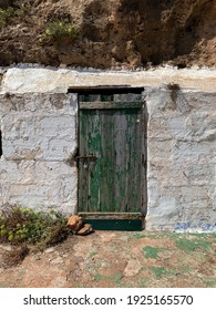 Binimel-la Beach, Minorca, Balearic Islands, September 2020: Green old wooden door with flaking paint and rusty lock from an abandoned fishermen shelter by the sea