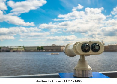 Binocular on viewing platform, selective focus, view of city and sky with clouds. Travel, sightseeing, tourism theme.
