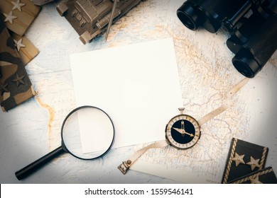 Binoculars, compass, magnifying glass, toy military tank, Soviet military chevrons lying on the world map with white paper in the center of the image for text.nobody.Flat lay.
