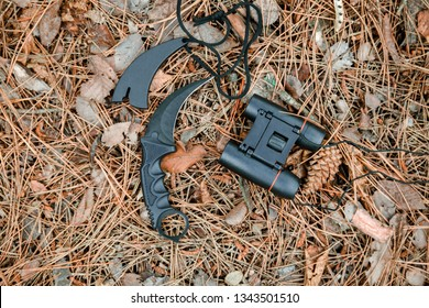 binoculars and karambit knife on the ground covered with pine needles