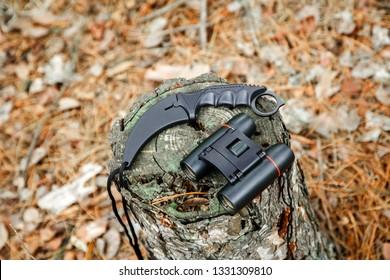 binoculars and karambit knife on the stump in autumn forest