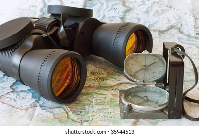 binoculars and magnetic compass on the opened map