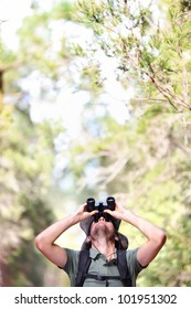 Binoculars - man hiker looking up at copy space during outdoors hiking trip.