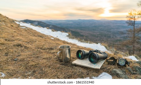 Binoculars map compass and mug on the background of nature mountains in the sunset. The concept of a halt, tourism travel, trip. Navigation, route - Shutterstock ID 1861551940