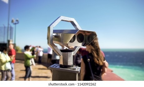 Binoculars at observation deck on sunny day, people on background looking at sea