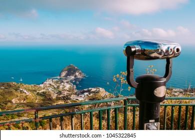 Binoculars on hill with beautiful Sant Angelo seaview on the horizon, Ischia island, Italy.