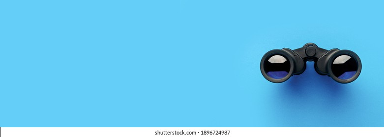 Binoculars on a light blue background. Banner. Flat lay, top view.