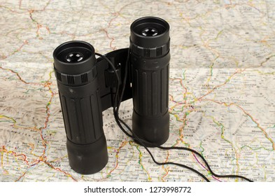 Binoculars on a paper map, a travel and adeventure concept