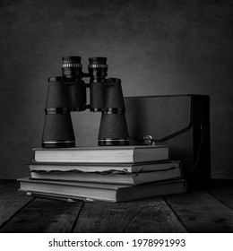 Binoculars on a stack of field guides