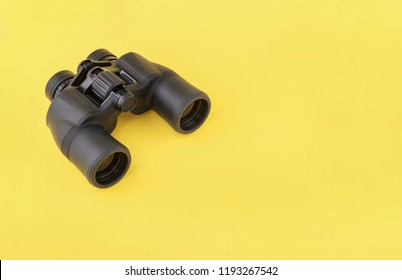 Binoculars on yellow background