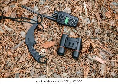 binoculars, radio set and karambit knife on the ground covered with pine needles