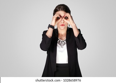 Binoculars sign .Woman have a bad sight. Looking far away and don't see. Studio shot, indoor. Isolated on grey background