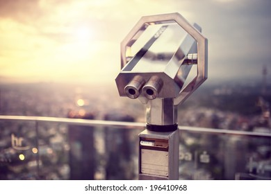 Binoculars or telescope on top of skyscraper at observation