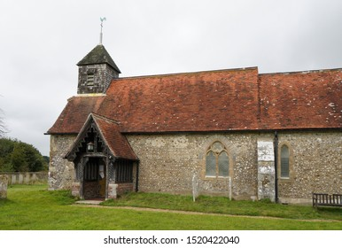 Binsted, Sussex / UK - 25 Sept 2019: St Marys, a small English village church dating from 12th Century with red pitched tiled roof, covered entrance porch and bell tower. Option 5a Arundel bypass.