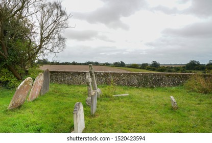 Binsted, Sussex / UK - 25 Sept 2019: Grave stones in a grassy graveyard of St Marys, a 12th Century village church. Beyond the flint wall, under a cloudy sky, the fields at risk from Option 5a bypass.