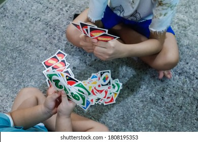 Bintaro / Indonesia - September 1, 2020: Children are holding and playing UNO card game for entertainment time at home