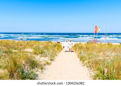 BINZ BEACH, RUGEN ISLAND - MAY 31, 2018:  Older couple of people walking back from beach in Baabe village, Baltic Sea, Germany. Beach holidays are popular among eldelry Germans.