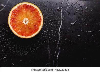 Bio bloody oranges cut in half on marble board. Top View
