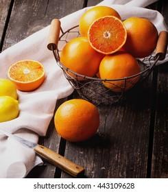 Bio bloody oranges and lemons in the basket on rustic wooden board, cut in halves. Top View