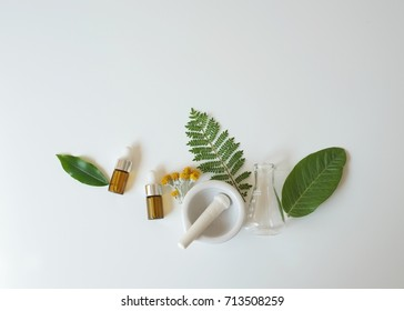 The bio laboratory glassware and blank cosmetic bottle containers with herbal flower ingredient,package for branding.Natural organic beauty skincare product concept. alternative medicine.Spa top view.