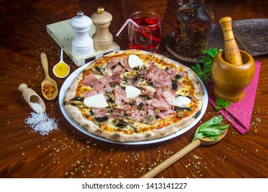 Bio pizza with mozzarella, mushroom, cheese and tomato. Presented with spicy oil and several decorative elements. Served on a round wooden table.
