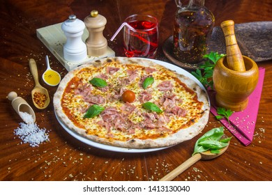 Bio pizza Romana with ham, cheese, tomato and basil. Presented with spicy oil and several decorative elements. Served on a round wooden table.
